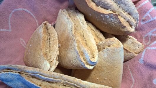 Kulhollinen taskuleipiä. Leivinliina pitää leivät lämpiminä ja ennen kaikkea näyttää kivalta.