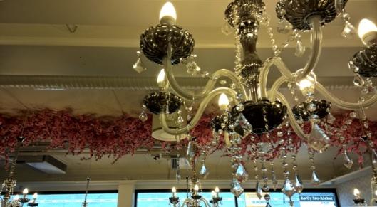 Puutarhatuolien ja -pöytien päällä roikkuu kruunuja ja vaalenpunaisia kukkaköynnöksiä. Vaikutelma on ihan vänkä.